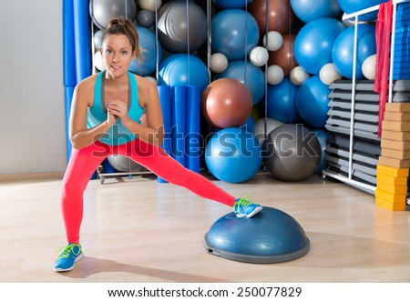bosu one leg squat girl exercise at gym workout and swiss ball background - stock photo