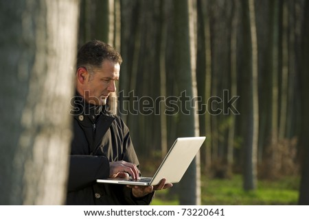 Botanist working with laptop inside a poplar wood - stock photo