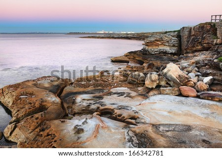Botany Bay Australia at dawn with lovelyl sandstone rocks  in the foreground and the pink and blue sky hues reflected in it's serene waters.  Botany Bay was the bay of Captain Cook's first landing    - stock photo