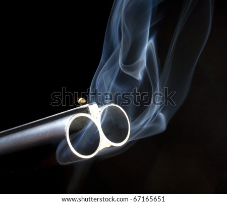 Both barrels on a double barreled shotgun that are smoking - stock photo