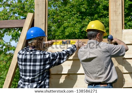 Both male and female workers who are building a wooden chalet - stock photo
