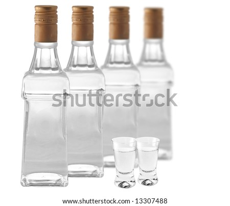 Botlles of vodka and shotglasses on white background
