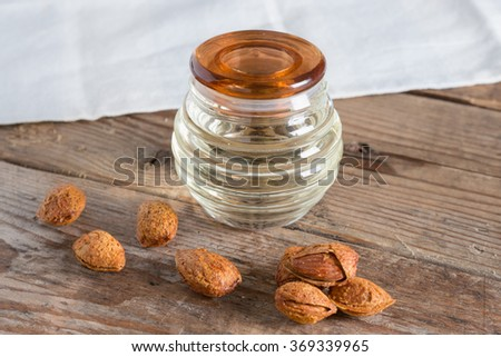 Bottle almond oil and almond kernel on wood background. - stock photo