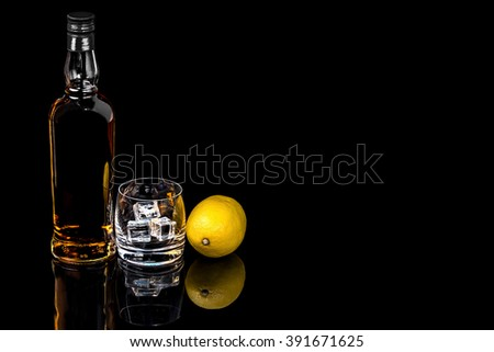 Bottle and a glass of whiskey with ice and  lemon on a black background - stock photo