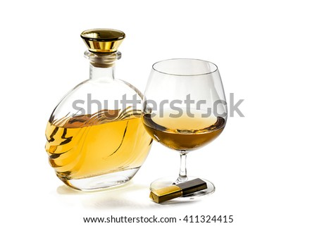 Bottle and a goblet of brandy with a chocolate on a white background - stock photo