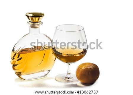Bottle and a snifter of brandy with  a mandarin on a white background - stock photo