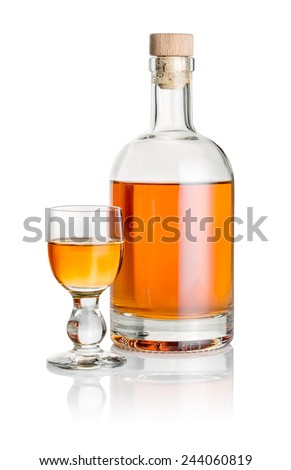 Bottle and glass goblet filled with amber liquid - stock photo