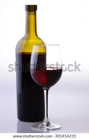 bottle and glass goblet full of dessert or rough red wine vinous colour standing together in studio isolated on white and grey background, vertical picture