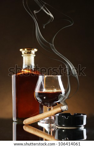 bottle and glass of brandy and cigar on brown background - stock photo