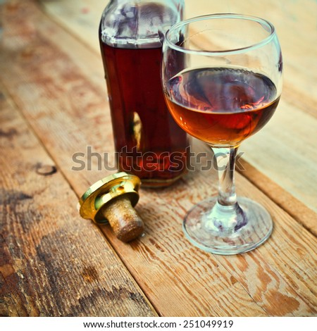 bottle and glass of cognac with ice on a wooden background - stock photo