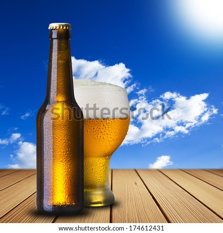 Bottle and Glass of Cold Beer on wood table with summer scene background