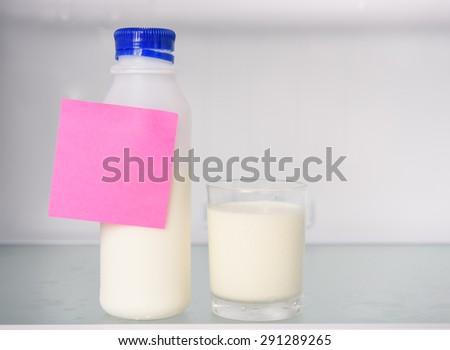 Bottle and glass of milk with postit  in refrigerator  - stock photo