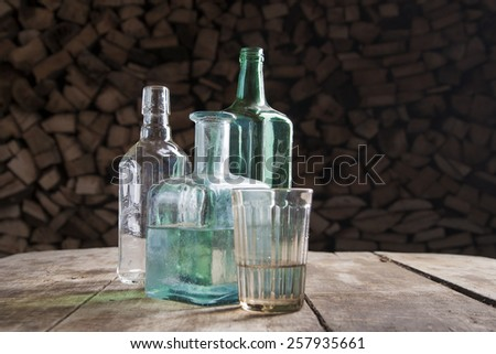 Bottle and glass of moonshine or vodka on the table