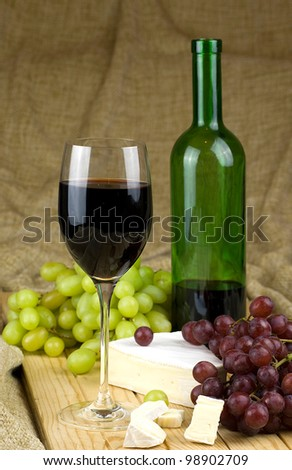 bottle and glass of red white grapes and brie cheese on brown background