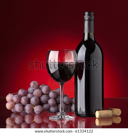 Bottle and glass of red wine, grape and cork on a red background - stock photo