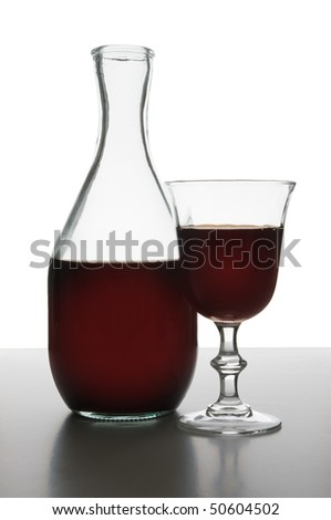 Bottle and glass of red wine in studio - stock photo