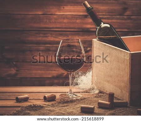 Bottle and glass of red wine on a wooden table  - stock photo