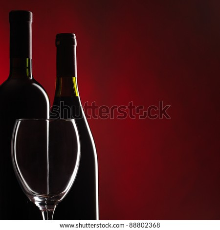Bottle and glass of red wine on dark red background