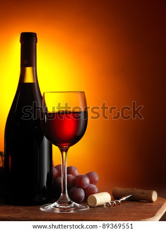 Bottle and glass of red wine on dark red background - stock photo
