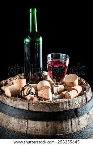 Bottle and glass of red wine on old barrel with stopper