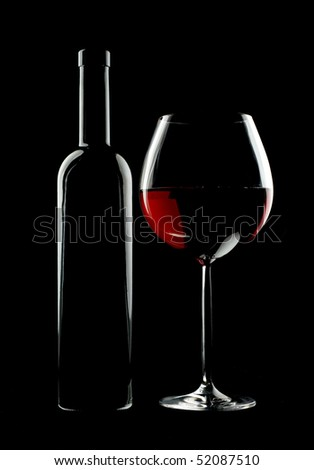 Bottle and glass of red wine over black background.