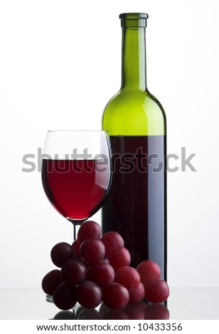 Bottle and glass of red wine with grapes on white backround - stock photo