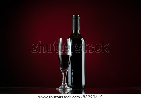 Bottle and glass of red wine with red background - stock photo