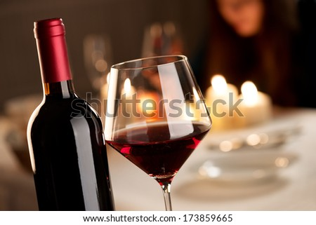 Bottle and glass of red wine with restaurant on background. - stock photo