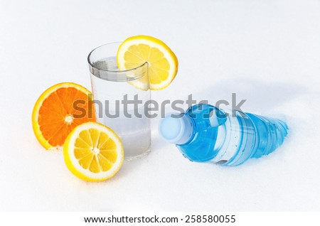 Bottle and glass of water in the snow with lemon and orange - stock photo