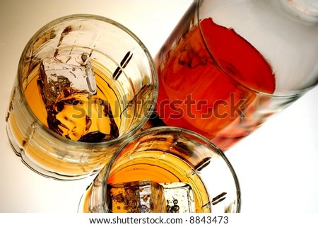 Bottle and glass of whiskey and ice against white background. - stock photo