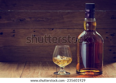 bottle and glass of whiskey  on a wooden background made with vintage tones - stock photo
