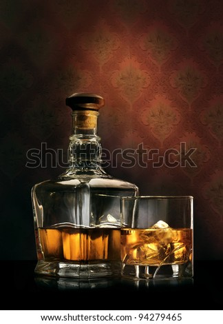 Bottle and glass of whisky with ice on wallpaper background - stock photo