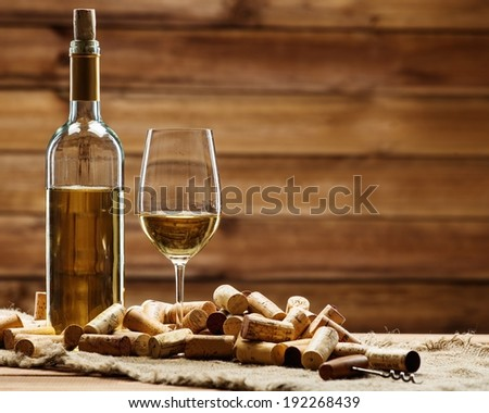 Bottle and glass of white wine on a wooden table among corks  - stock photo