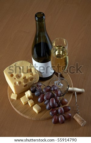 Bottle and glass of white wine with cheese, grapes, a cork and a corkscrew on a wood background