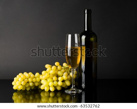 Bottle and glass of white wine with grapes against dark background