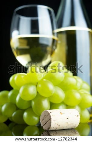 Bottle and glass of white wine with grapes and cork on black background, selective focus - stock photo