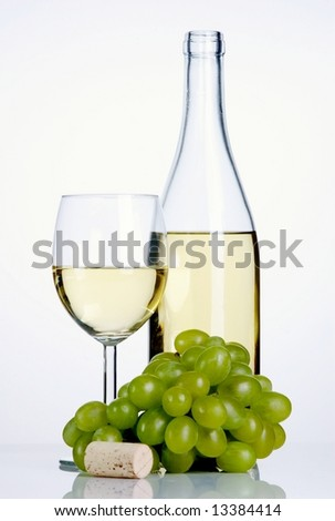 Bottle and glass of white wine with grapes and cork on white background