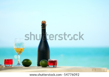 Bottle and glass of wine on the beach - stock photo