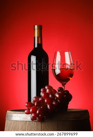 Bottle and glass of wine with grapes on wooden barrel - stock photo