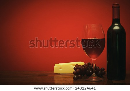 Bottle and glass of wine with red grapes and cheese a retro photo