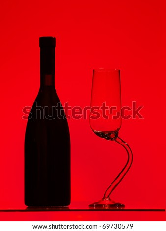 Bottle and glass over red background
