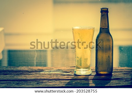 bottle and glass with beer on wood table - stock photo