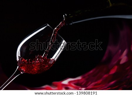 bottle and glass with red wine on a black background - stock photo