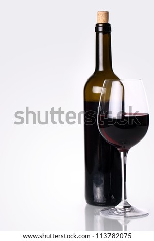 Bottle and glass with red wine on the table - stock photo