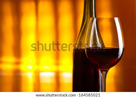 bottle and glass with red wine on  yellow background - stock photo