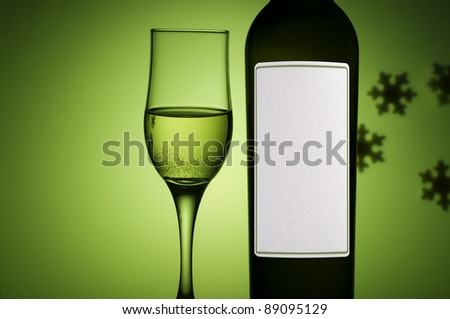 bottle and glass with white wine on green background - stock photo