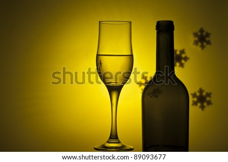 bottle and glass with white wine on yellow background - stock photo