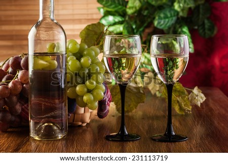 Bottle and glasses of white wine and bunches of grapes