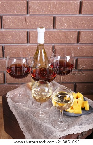 Bottle and glasses of wine and cheese on table on brick wall background - stock photo