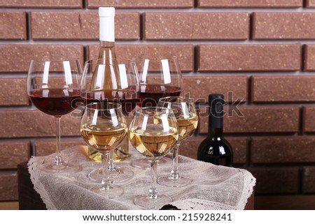 Bottle and glasses of wine on table on brick wall background - stock photo